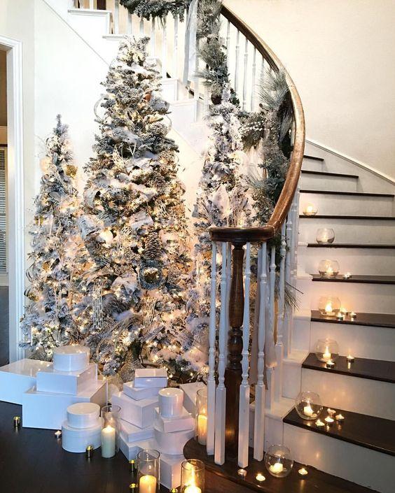 un ingresso da favola invernale chic con alberi di Natale affollati, luci e ornamenti neutri più candele in giro
