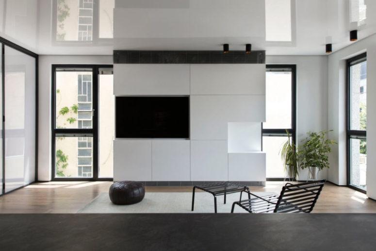 Il soggiorno è realizzato con un elegante mobile TV bianco e una TV integrata, una sedia, un poggiapiedi e un pouf in pelle