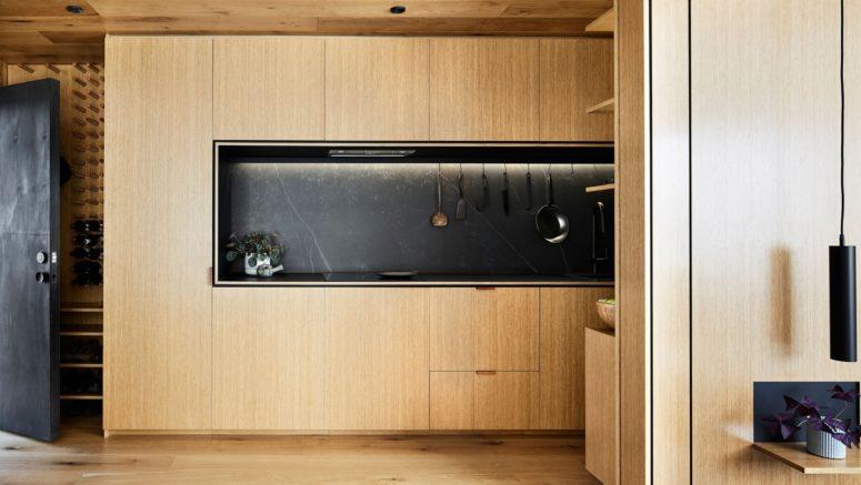 La cucina è realizzata con eleganti armadi in legno di colore chiaro e un alzatina in marmo nero per un'atmosfera elegante