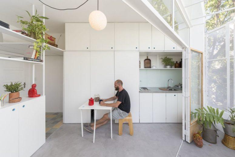 L'appartamento dispone di una cucina bianca elegante con un piccolo spazio per mangiare che può essere nascosto