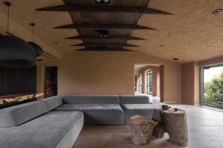 Il soggiorno è unito alla sala da pranzo, il soffitto è in legno e i tavolini in legno