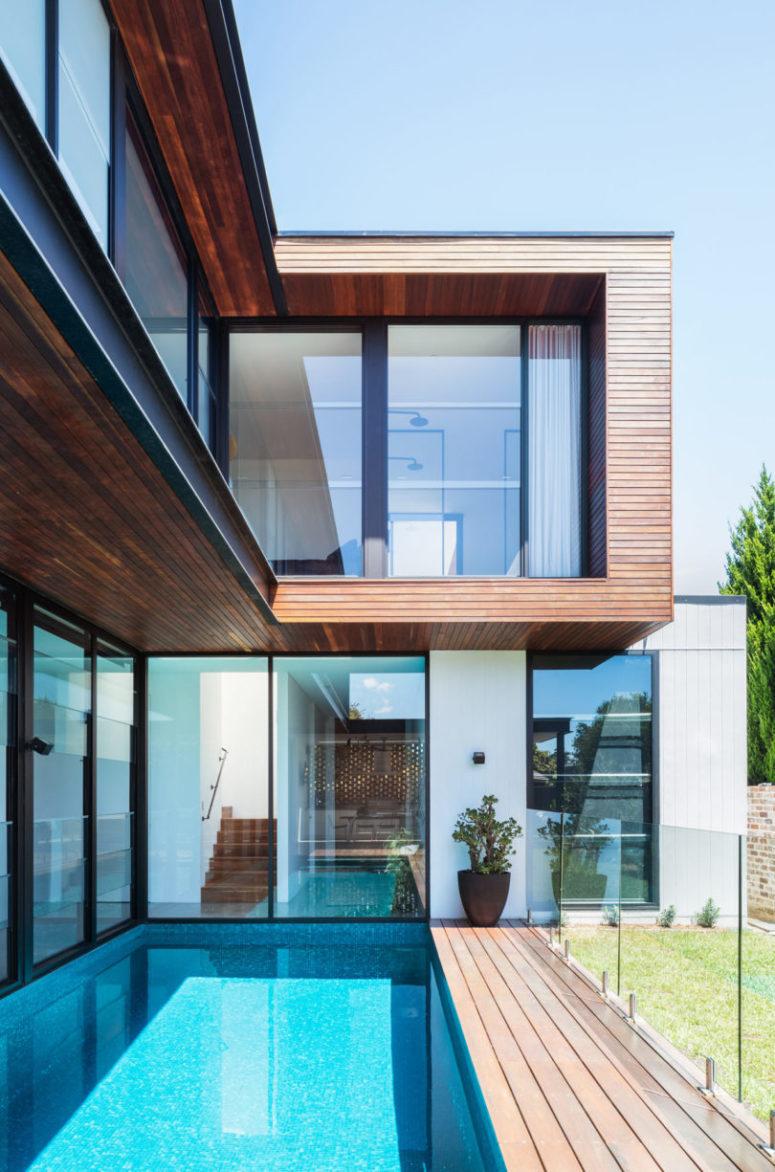 Questo piccolo cortile con una piscina stretta e un ponte è coperto da una recinzione di vetro