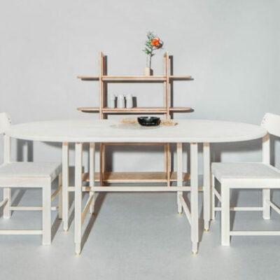 Si tratta di un tavolo da pranzo, sedie e uno scaffale a giorno che presentano tutti gambe simili e angoli curvi che sono caratteristiche della collezione
