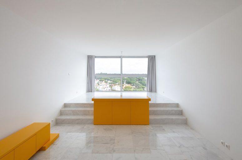 L'appartamento presenta una disposizione di elementi architettonici di base in giallo audace e lo spazio è creato intorno a loro