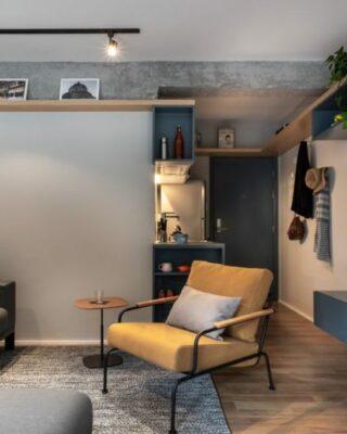 Il soggiorno è fatto in blu e grigio, con mobili imbottiti e in pelle, con luci e uno spazio per l'home office
