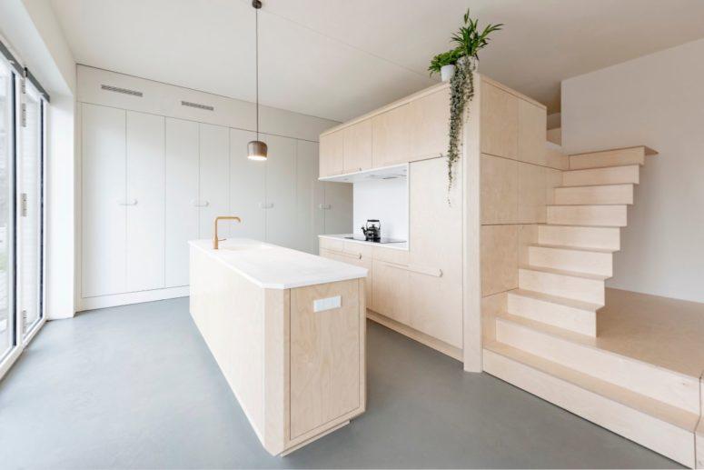 L'isola della cucina si abbina al mobile contenitore e alla zona letto a soppalco creando uno spazio coeso con un tocco moderno