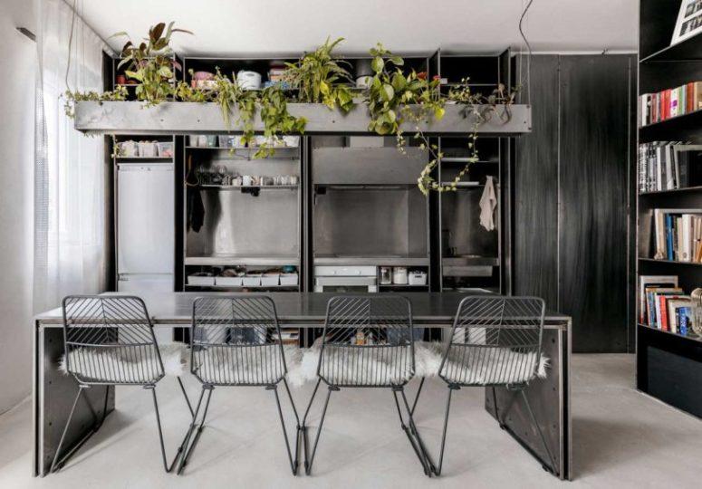 La cucina è in metallo, tutti gli elettrodomestici, un tavolo e sedie in metallo più una fioriera in cemento sopra